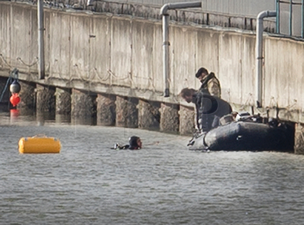 © Licensed to London News Pictures. 12/02/2018. London, UK. Members of the Royal Navy Bomb Disposal Team look on as one of their colleagues surfaces (L) after diving at the location of the unexploded bomb next to London City Airport which remains closed. A World War II era bomb was found in The River Thames during routine work on nearby King V Dock. Police have evacuated nearby residents, closed the airport and set up a 214-metre exclusion zone. Photo credit: Peter Macdiarmid/LNP