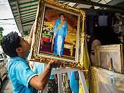 10 AUGUST 2016 - BANGKOK, THAILAND: A worker puts up a portrait of Queen Sirikit of Thailand in front of a shop in Bangkok. Thais are preparing for the Queen's birthday. Queen Sirikit of Thailand, was born Mom Rajawongse Sirikit Kitiyakara on 12 August 1932. She married  Bhumibol Adulyadej, King of Thailand (Rama IX) in 1950. He is the longest serving monarch in the world and she is longest serving consort of a monarch. Her birthday, like the King's Birthday (which falls on Dec. 5),  is a national holiday in Thailand. Her birthday, August 12, is also celebrated as Mothers' Day in Thailand. Thais hang portraits of Queen Sirikit in their homes and fly her royal flag on her birthday.        PHOTO BY JACK KURTZ