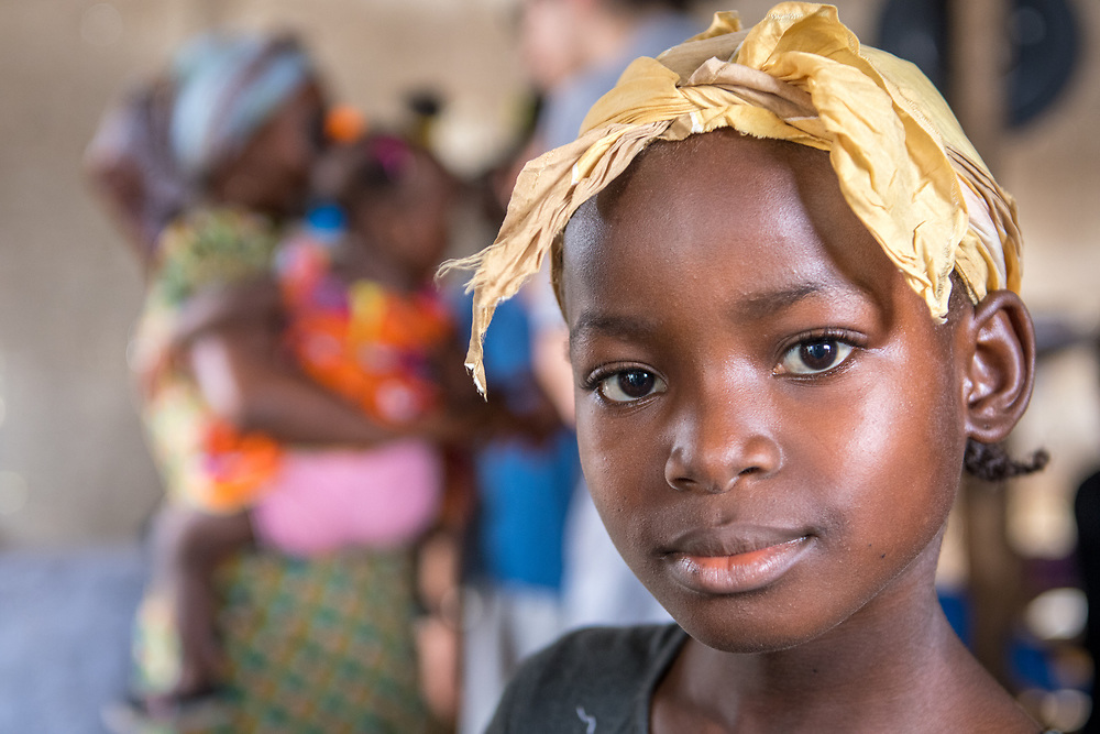 A close up image of a young girl with a wrap on her head and a woman holding a child in the background in Ganta, Liberia