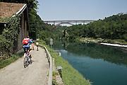 Pista ciclabile lungo il fiuma Adda a Paderno d'Adda. Sullo sfondo il ponte in ferro di Paderno..Bicycle path along Adda river, background the iron bridge of Paderno.