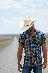 African American cowboy outdoors on a dirt road
