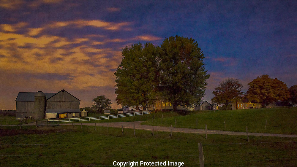 Kerosene lights burn in an Amish Farm House as the farmer works in his barn.