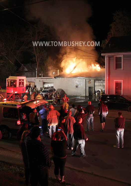 Middletown, New York - People gather on the street as firefighters work at the scene of a fire at The Engine Shop on North Street in Middletown late on the night of Friday, April 20, 2012.