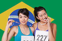Portrait of smiling young medalists standing against Brazilian flag