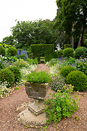 A stone urn surrounded by herbaceous borders in the blue and white garden at Cothay Manor, Greenham, Wellington, Somerset, UK