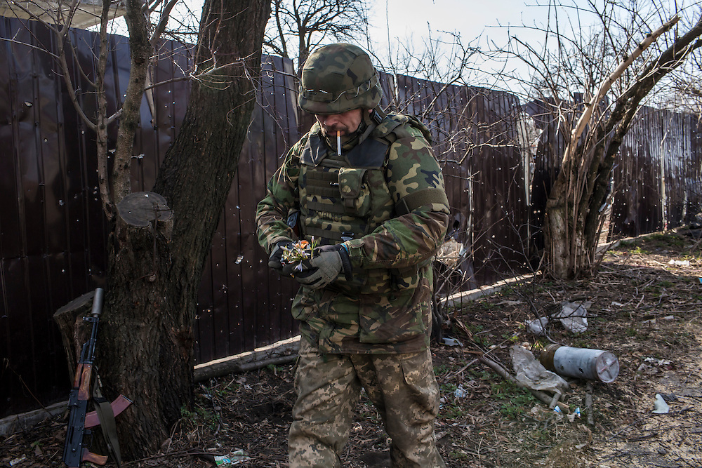 PISKY, UKRAINE - MARCH 20, 2015: Volodya, a fighter for the Dnipro-1 battalion, a pro-Ukrainian militia, with flowers he picked for his wife in the heavily contested town of Pisky, Ukraine. CREDIT: Brendan Hoffman for The New York Times