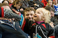 KELOWNA, CANADA, FEBRUARY 15: A Kelowna Rockets fan high fives Rocky the Racoon at the Kelowna Rockets on February 15, 2012 at Prospera Place in Kelowna, British Columbia, Canada (Photo by Marissa Baecker/Shoot the Breeze) *** Local Caption ***