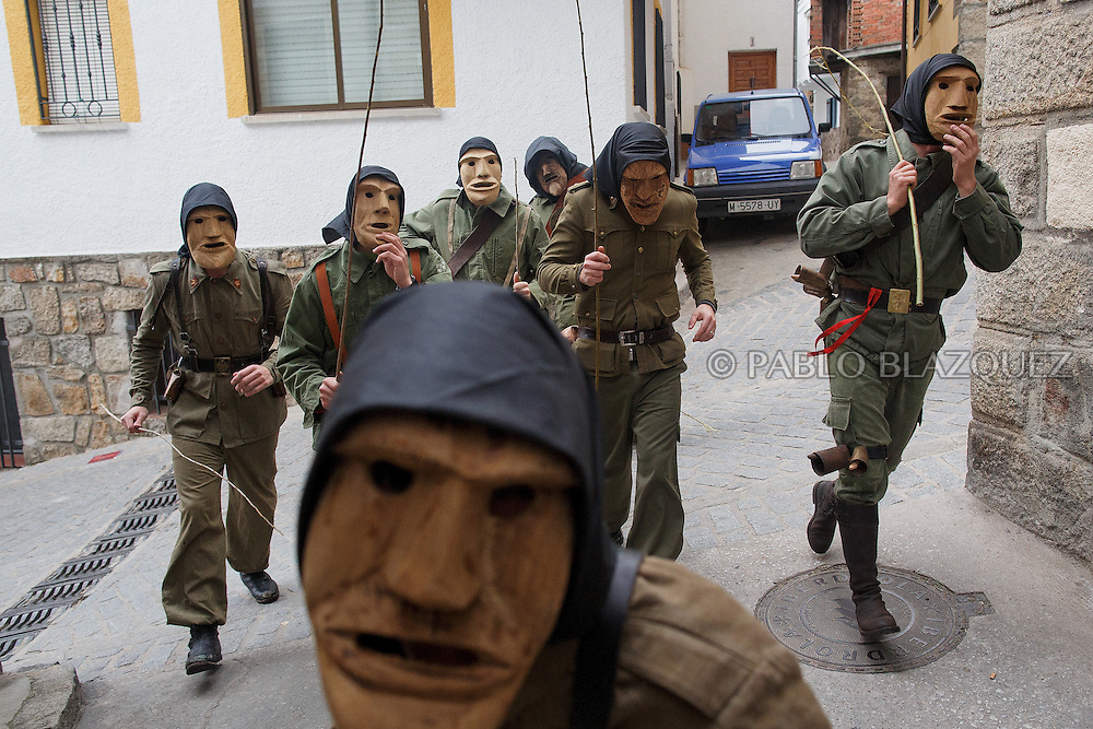 The Machurreros from Pedro Bernardo run along the streets during Carnival on February 6, 2016 in Pedro Bernardo, in Avila province, Spain. The origins of this pagan festival are unknown. The Machurreros wear wood masks, a military dress, black handkerchief, cowbells, and hold wicker stick. The festival disappeared after Dictator Franco forbid carnival festivals in 1937, but it was recently recovered. Before disappearing, male villagers after the military service, used to dress as Machurreros as they run along the streets scaring children and adults with their wicker stick to bring fertility to the land and expel the evil spirits. (© Pablo Blazquez)