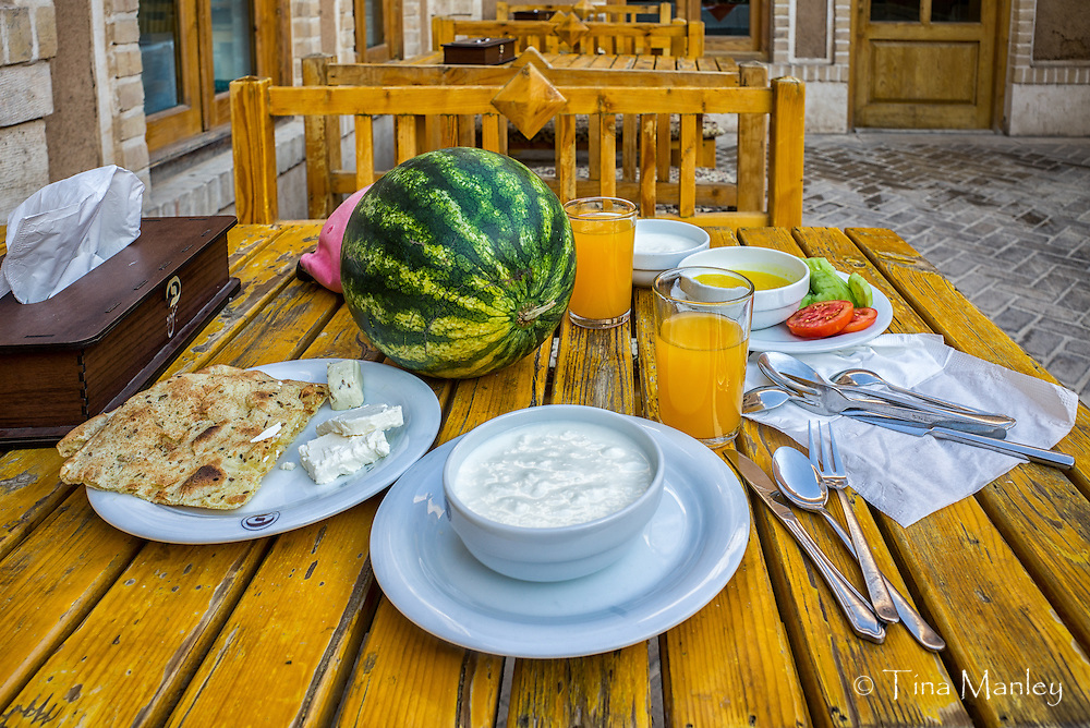 A breakfast of fresh fruit, bread, cheese, and yogurt at the Dad Hotel in Yazd, Iran.