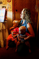 Wendy Jeub holds daughter Priscilla, 1 (L) and son Zechariah, 4 months, while watching a daughter open birthday presents in Monument, Colorado July 17, 2009. Quiverfull believers Wendy and Chris Jeub have 15 children and would be happy to have more if God wills it they say. REUTERS/Rick Wilking (UNITED STATES)