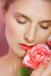 Close up of Young Woman Holding Rose to her Lips
