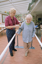 Female occupational therapist or physiotherapist assisting elderly woman to improve her balance through walking exercises, H