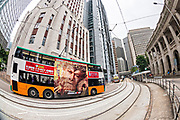 Fisheye view of a double decker bus traveling past the Old Bank of China building in the central district of Hong Kong.