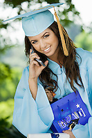 Graduate Using Cell Phone and holding gift bag outside portrait