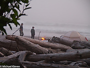 Two campers behind the driftwood watch the waves near there tent at Second Beach