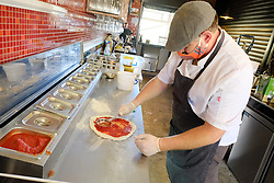 JOHANNESBURG SOUTH AFRICA - MAY 01 Delta Cafe and DQ owner Daniel Basch prepares pizza for delivery on May 01, 2020 in Johannesburg South Africa. South Africa moved down to Level 4 of the national lockdown with relaxed restrictions as part of a risk adjusted 5 stage phasing of lockdown measures. This includes allowing of certain restaurants to reopen for trade and prepare hot food as delivered takeaway only. (Photo by Gallo Images/ Dino Lloyd)