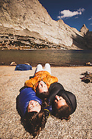 Mother, son and daughter cuddle up during a cool September day on the shores of Deep Lake, Wind River Mountains, Wyoming.