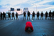 "July 11, 2016 - Pastor Rickey Scott, 44, with New Change Church, kneels as he prays in front of Memphis police officers during a Black Lives Matter protest on I-40 in Memphis on Sunday. ""Black power and Black Lives Matter movement is good but we need Jesus's power,"" Scott said. ""That's the most educational thing we can tell them that Jesus life matters."" (Yalonda M. James/The Commercial Appeal)"