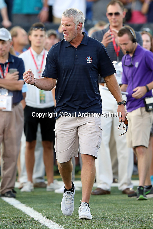 Former Green Bay Packers quarterback Brett Favre pumps his fist while being announced over the public address system as he walks onto the field as a new member of the Pro Football Hall of Fame before the 2016 NFL Pro Football Hall of Fame preseason football game against the Indianapolis Colts on Sunday, Aug. 7, 2016 in Canton, Ohio. The game was canceled for player safety reasons due to the condition of the paint on the turf field. (©Paul Anthony Spinelli)
