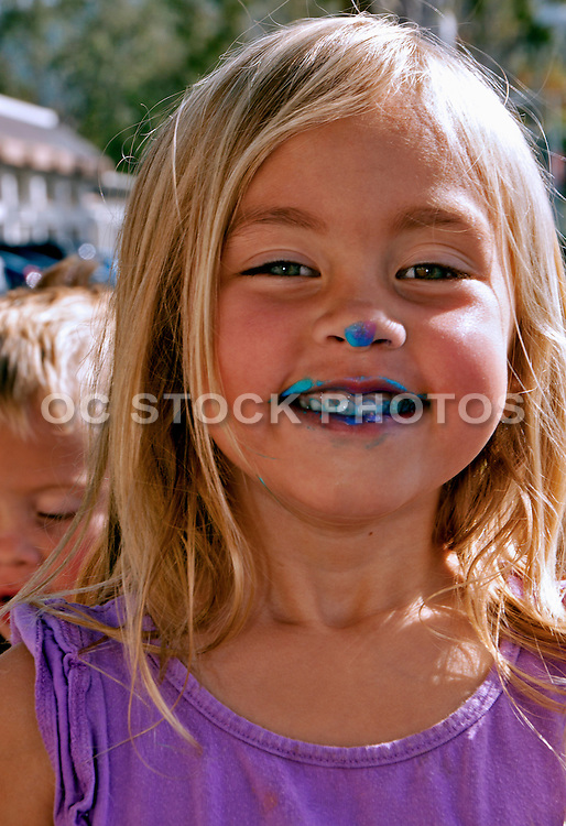cute blonde girl with frosting on her nose and mouth socal stock