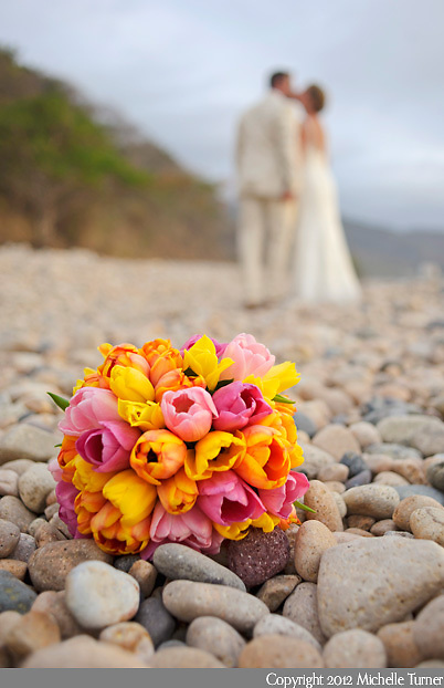 A beach wedding with a bouquet full of tulips in Puerto Vallarta, Mexico.  Image by Puerto Vallarta Wedding Photographer Michelle Turner.