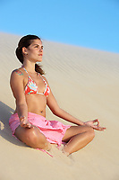 beautiful smiling bikini dressed young brazilian  woman meditating on lotus posture on the sand dune of  jericoacoara ceara state near fortaleza