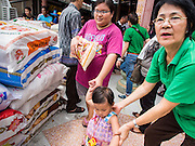 "07 AUGUST 2014 - BANGKOK, THAILAND:  A woman and her child carries a sack of rice away from a food distribution at Pek Leng Keng Mangkorn Khiew Shrine in Bangkok. Thousands of people lined up for food distribution at the Pek Leng Keng Mangkorn Khiew Shrine in the Khlong Toei section of Bangkok Thursday. Khlong Toei is one of the poorest sections of Bangkok. The seventh month of the Chinese Lunar calendar is called ""Ghost Month"" during which ghosts and spirits, including those of the deceased ancestors, come out from the lower realm. It is common for Chinese people to make merit during the month by burning ""hell money"" and presenting food to the ghosts. At Chinese temples in Thailand, it is also customary to give food to the poorer people in the community.       PHOTO BY JACK KURTZ"