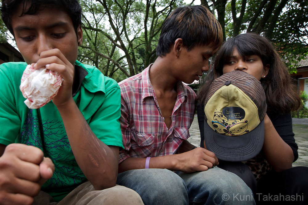 Street children Krishna, left, Vivek and Biddha sniff glue to get high at park in Kathmandu, Nepal on Aug 20, 2012. Biddha, 16, is 5 month pregnant. There are estimated around 5,000 street children working and living on the streets of Nepal and the number continues to grow with roughly 300 to 500 children leaving home every year. Some do so because of abusive, alcoholic parents, maltreatment at home, and the temptation to earn more money. They often end up taking drugs, abusing alcohol, and even suffering sexual abuse by locals and foreign tourists..(Photo by Kuni Takahashi)