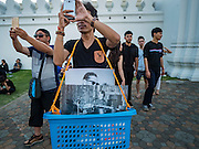 15 OCTOBER 2016 - BANGKOK, THAILAND:  A man selling portraits of Bhumibol Adulyadej, the King of Thailand, on a street in front of the Grand Palace uses his smart phone to take a picture of the Ministry of Defense building in Bangkok. King Bhumibol Adulyadej died Oct. 13, 2016. He was 88. His death comes after a period of failing health. With the king's death, the world's longest-reigning monarch is Queen Elizabeth II, who ascended to the British throne in 1952. Bhumibol Adulyadej, was born in Cambridge, MA, on 5 December 1927. He was the ninth monarch of Thailand from the Chakri Dynasty and is known as Rama IX. He became King on June 9, 1946 and served as King of Thailand for 70 years, 126 days. He was, at the time of his death, the world's longest-serving head of state and the longest-reigning monarch in Thai history.     PHOTO BY JACK KURTZ