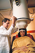 "Scripps Medical Center: Brain magnetic response. A woman undergoing a brain scan with a neuromagnetometer, to measure normal brain function. The non-invasive scanner is positioned above her head while she views an object. This scan technique is called magneto encephalography (MEG). The neuromagnetometer measures magnetic fields generated from nerve cell activity within the brain. The scanner contains sensitive magnetic field detectors known as SQUIDS (Superconducting Quantum Interference Devices). MEG enables high- speed nerve cell activity to be detected, to show the brain working in rapid ""real"" time. It assists researchers to understand the normal brain. MODEL RELEASED (1990)"