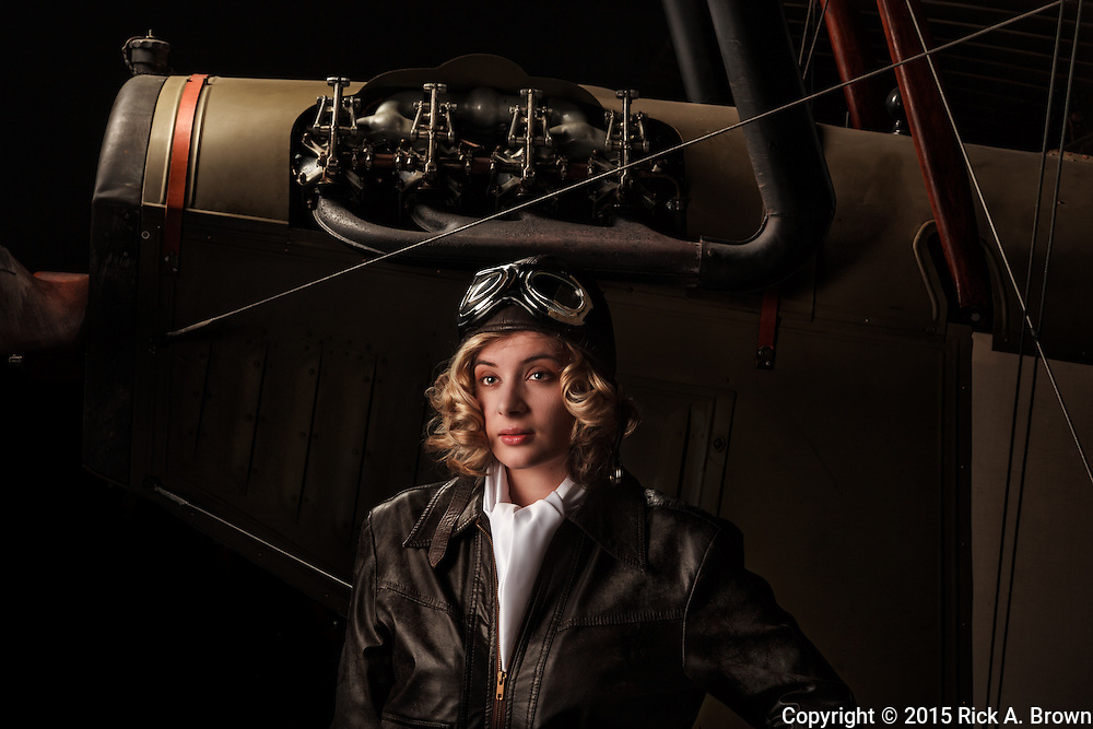 """A young model posing as a late twenties aviatrix with a Curtiss JN-4D """"Jenny"""" at WAAAM."""