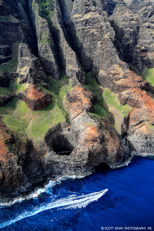 Aerial view of Na Pali coast, with puka hole, boat, Kauai, Hawaii