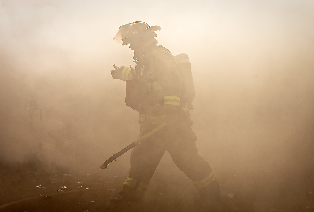 A Coeur d'Alene firefighter walks through smoke billowing from a house fire Monday on Howard Street north of Appleway. No one was injured in the fire which a cause is still being investigated.