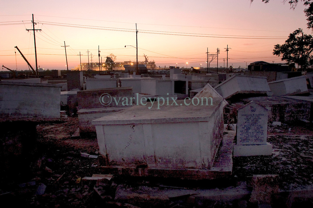 03 November, 2005. New Orleans, Louisiana. Post Katrina.<br />  Merrick Cemetery, St Bernard Parish just outside New Orleans, Louisiana in the aftermath of Hurricane Katrina. FEMA contractors are still removing coffins from the graveyard destroyed by the storm. Merrick cemetery was one of the earliest slave cemeteries in the south and was deluged by 20ft of flood water. Just beyond the smashed cemetery a cruise ship is moored alongside the Mississippi River, housing hundreds of recovery workers.<br /> Photo; &copy;Charlie Varley/varleypix.com