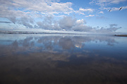 The sky, clouds and seagulls reflect in the wet sand of Fort Stevens state park beach in Oregon.