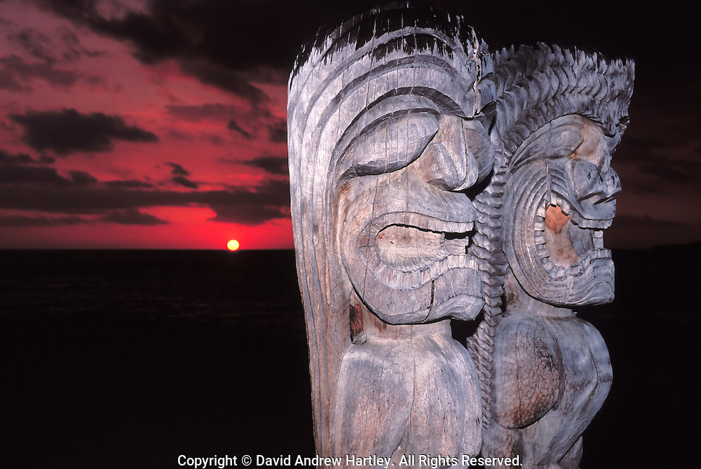 Ki'i stand guard as the sun sets below stormy skies, Pu'uhonua O Honaunau National Historic Park, Hawaii
