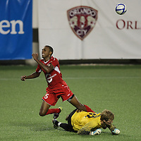 Orlando City Lions Forward Dennis Chin (15)gets tripped up by Goaltender Chase Harrison (23) during a United Soccer League Pro soccer match between the Harrisburg City Islanders and the Orlando City Lions at the Florida Citrus Bowl on August 12, 2011 in Orlando, Florida. The Orlando City won the match 4-0. (AP Photo/Alex Menendez)