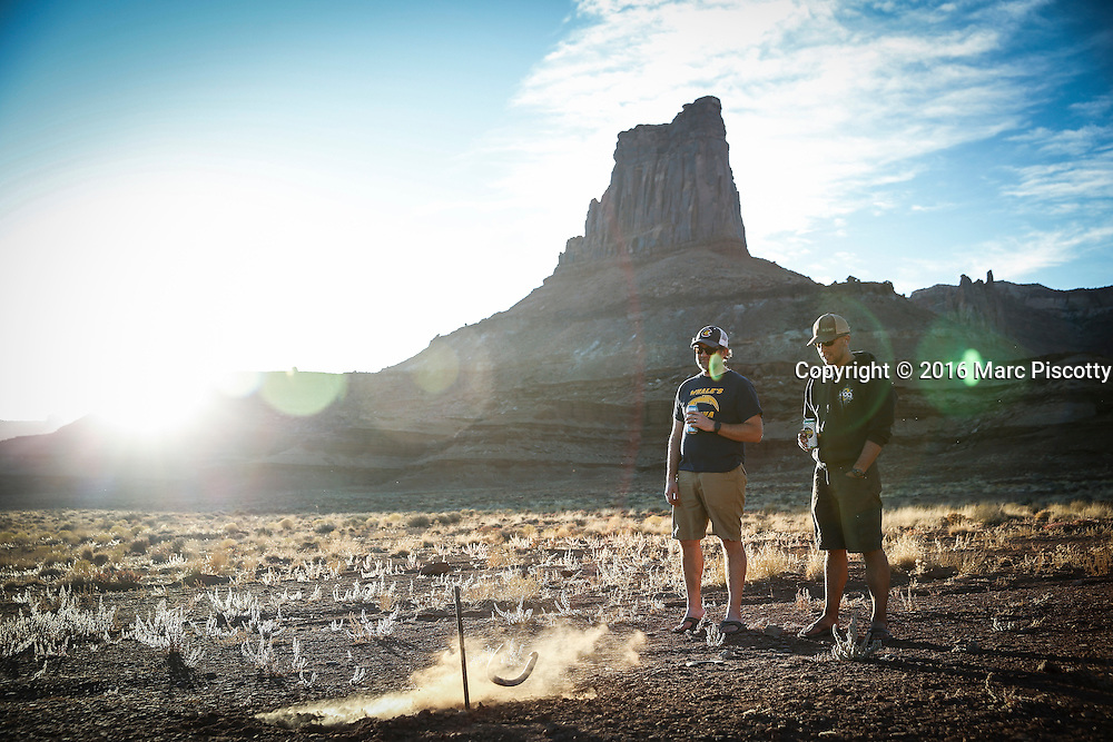 SHOT 10/16/16 5:52:15 PM - Tossing horseshoes after riding all day on the White Rim trip. The White Rim is a mountain biking trip in Canyonlands National Park just outside of Moab, Utah. The White Rim Road is a 71.2-mile-long unpaved four-wheel drive road that traverses the top of the White Rim Sandstone formation below the Island in the Sky mesa of Canyonlands National Park in southern Utah in the United States. The road was constructed in the 1950s by the Atomic Energy Commission to provide access for individual prospectors intent on mining uranium deposits for use in nuclear weapons production during the Cold War. Four-wheel drive vehicles and mountain bikes are the most common modes of transport though horseback riding and hiking are also permitted.<br /> (Photo by Marc Piscotty / &copy; 2016)