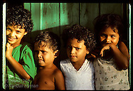 Four kids stand at door of home at Seringal Mourao, failed rubber tapper community on Eiru River. Brazil