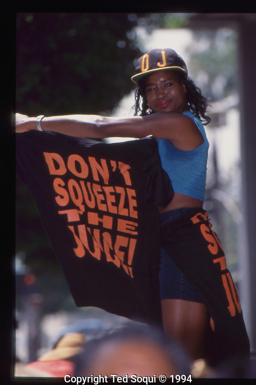 The OJ Simpson trial and media circus.<br /> A woman holding a &quot;Don't Squeeze the Juice!&quot; tee-shirt,