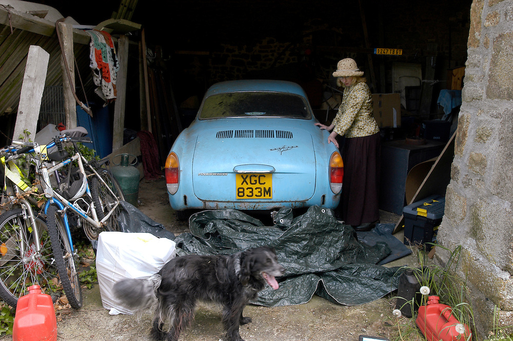For a story by Matt Saltmarsh on Brits leaving their French country homes...France, Saint-Siméon, approximately 250 kms. southwest of Paris, Patricia Mansfield-Devine, 46, a freelance writer, with an old British Karmann Ghia car in a barn of her French home. May 8, 2009...Photo © J.B. Russell for the International Herald Tribune