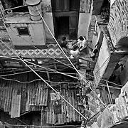 Neighbors try to catch some fresh air and play an afternoon game of chess sitting out on what is left of the second-story, inner-balcony floor of their deteriorating apartment building in Centro Havana, Cuba, 1999.  Photo by Jen Klewitz