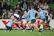 Scott Higginbotham (Rebels) is tackled by Bernard Foley (Waratahs) during the Round 15 match of the 2013 Super Rugby Championship between RaboDirect Rebels vs HSBC Waratahs at AAMI Park, Melbourne, Victoria, Australia. 24/05/0213. Photo By Lucas Wroe