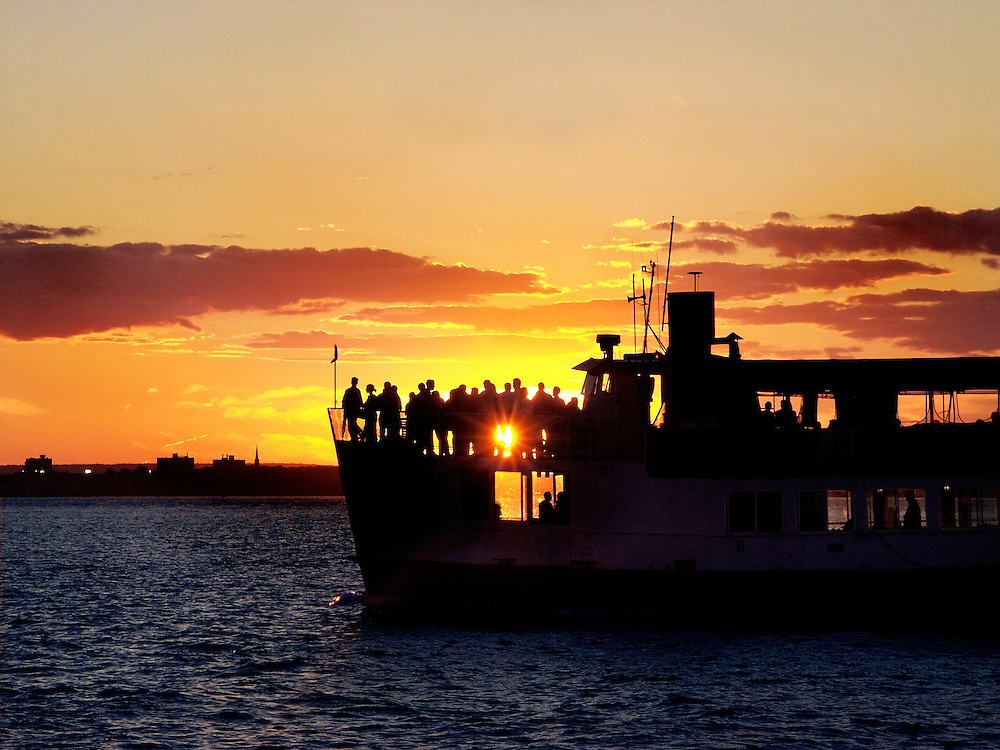 A tour boat passes by the setting sun on the Hudson River near Red Hook, Brooklyn.