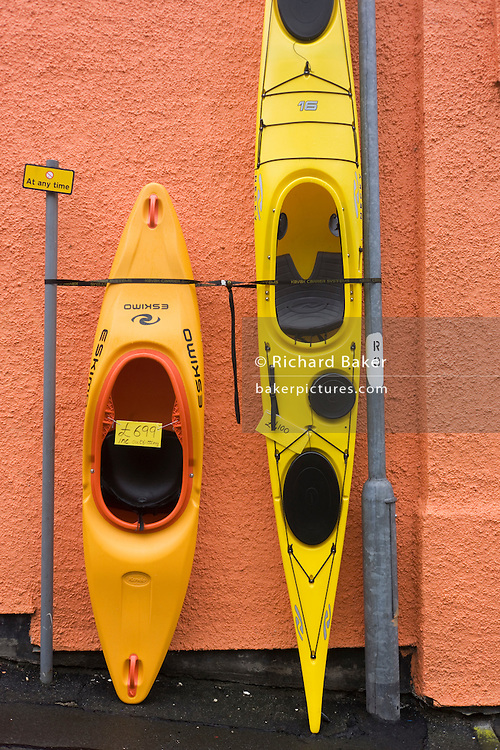 Kayaks and canoes stand upright against a shop wall in Oban, Scotland.