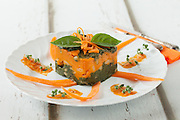 Bicolor gnocchi timbale with pumpkin and chard cream, decorated with fresh pumpkin and basil leaves.