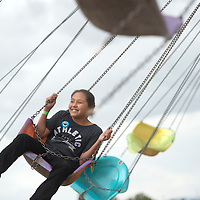 Michaela Silversmith rides on the swings at the Ramah Navajo Fair carnival Friday.