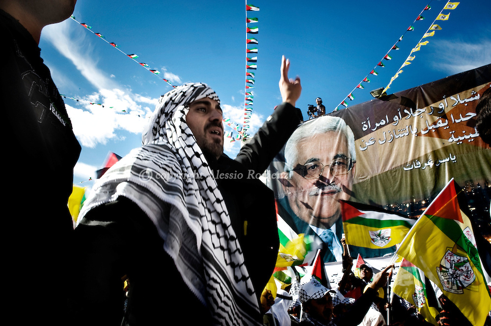 A Palestinian man flashes the victory sign next to a banner bearing the picture of President Mahmud Abbas during a rally marking the fifth anniversary of late Palestinian leader Yasser Arafat's death in the West Bank city of in Ramallah on November 11, 2009. The fifth anniversary of Arafat's death finds Palestinians more divided than ever and his successor Abbas pondering resignation because of stalled US-led peace efforts that have failed to bring about an independent Palestinian state..© ALESSIO ROMENZI