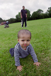 Father watching young son crawl across grass in park,