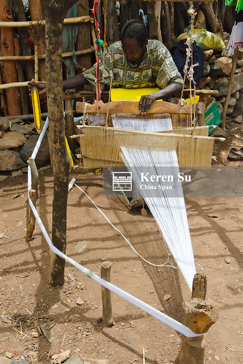 Konso Cultural Landscape (UNESCO World Heritage site), people weaving by loom in the village, Ethiopia